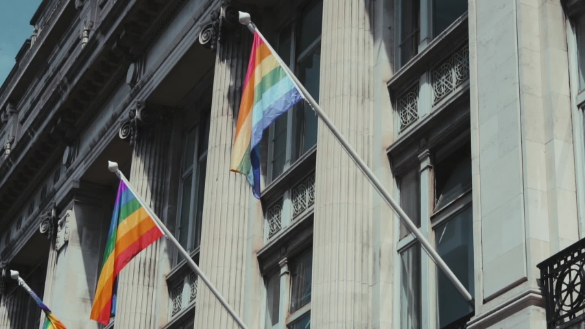 Low angle shot of rainbow pride flags waving from the building. Dublin Ireland | Shutterstock HD Video #1034581187