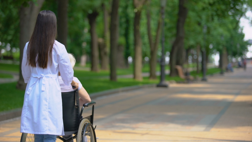 Female nurse walking in park with disabled patient, rehabilitation center #1034595647