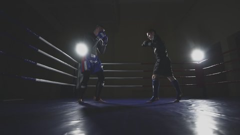 Boxers train before fight in ring. Muay thai fighters sparring in slow motion.