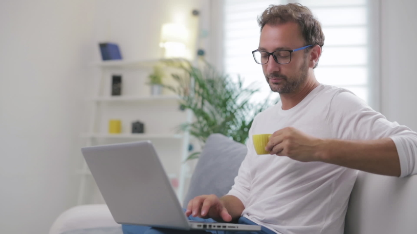 Man using laptop for video call in his living room. | Shutterstock HD Video #1034707397