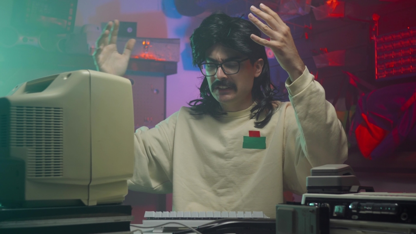 In the '80s or '90s.. A frustrated computer nerd slapping his personal computer and keyboard. Retro scene with vintage colors and atmosphere. | Shutterstock HD Video #1034714297