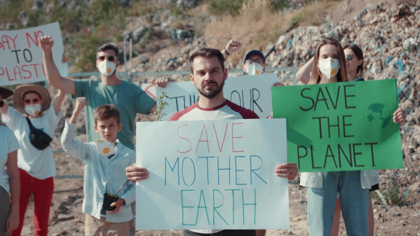 Portrait of young man fighting for nature holding save mother earth sign at dump. In backgeound his friends protesting against nature pollution waving hands calling on to save planet. #1034925827