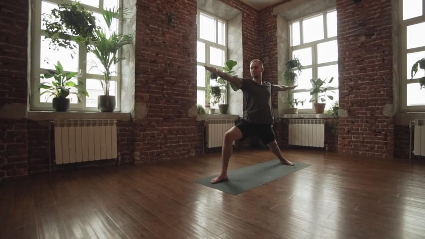 Man practice warrior yoga pose in studio with brick wall. Sporty man in shorts doing yoga indoors with wooden floor and big windows with copyspace. Wide angle   Shutterstock HD Video #1034995247