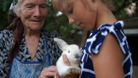 Teenager girl holds a white rabbit in her arms, her grandmother is standing nearby. Breeding rabbits, rabbit farm. Happy childhood
