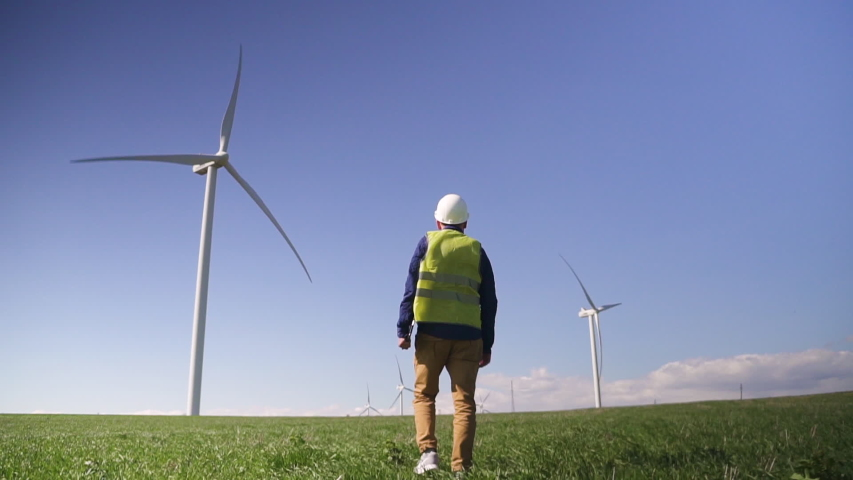 Adult or mature technician man in white hard hat and green uniform wear walking with modern digital tablet wind mill power station on background with blue sky. Male monitoring system performance