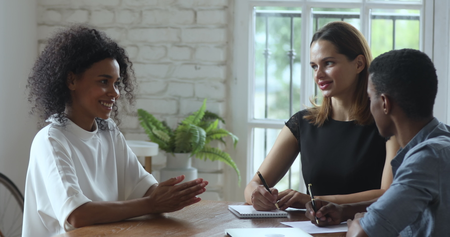 African female job applicant talk to diverse hr team at interview business meeting, american mentor teach interns make notes training new workers at office meeting, apprentice and recruitment concept | Shutterstock HD Video #1035023897