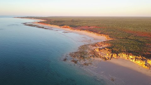 Scenic panoramic aerial drone view at sunset of flight high above ocean and remote beach in Western Australia, with rocky cliff coastline, summer sunny blue sky and horizon as background and copy spac