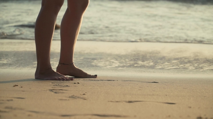 Close-up of legs of young woman walking along tropical beach at sunset. Foamy sea waves gentrly wash sand and feet, warm soft evening sun reflects on wet surface. Slow motion footage. | Shutterstock HD Video #1035083627