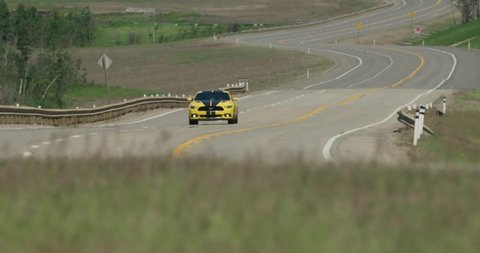 Dunvegan , Alberta / Canada - 06 20 2019: Ford Mustang drives by at high speed near Dunvegan Alberta on highway. Camera pans as car drives by.