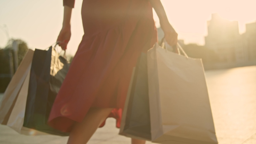 Woman in red dress with shopping bags walking in a city at sunset. Slow motion