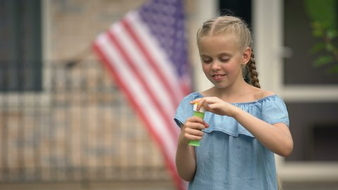 Positive girl blowing soap bubbles, careless and happy childhood, leisure time