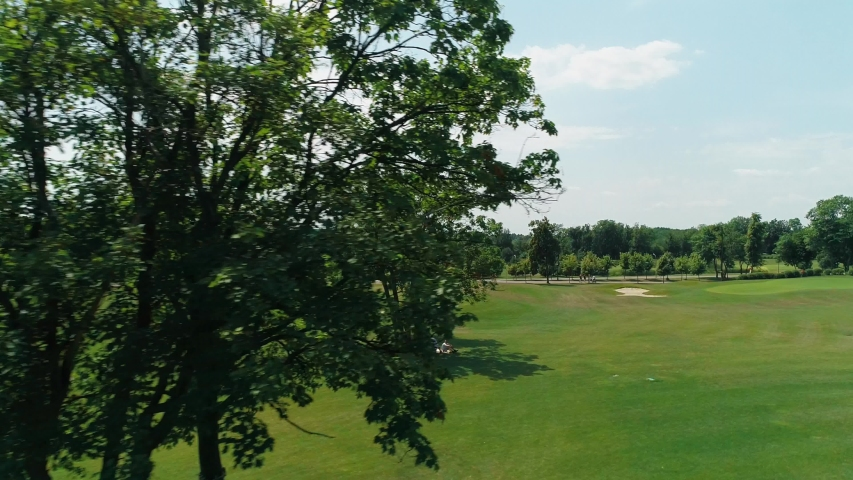 Aerial view of a green golf course with beautiful trees and forest, blue sky with clouds on sunny day in the summer time. 4K drone footage.   Shutterstock HD Video #1035175847