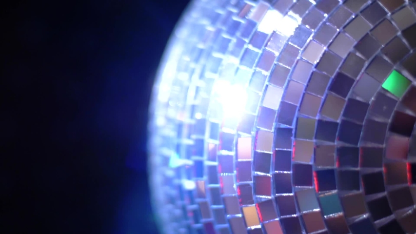 Party Light music disco ball changing hue on black background. Rotating sparkling mirror disco ball rotating in nightclub lights, festive party atmosphere, fun. Concept of night party. | Shutterstock HD Video #1035212777