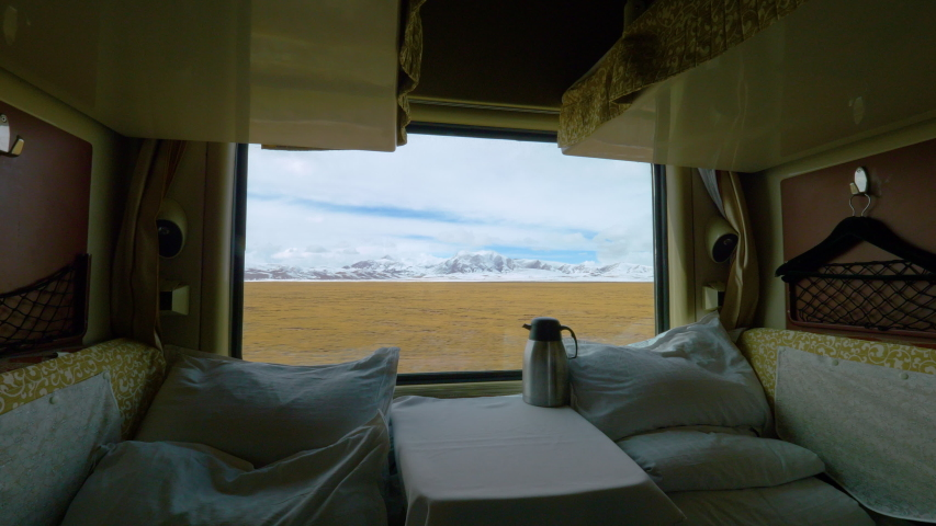 CLOSE UP: Scenic view of the vast Tibetan plains through the window of a first class overnight train. Spectacular view of beautiful Himalaya in the distance from the comfort of private sleeping cabin. | Shutterstock HD Video #1035233567