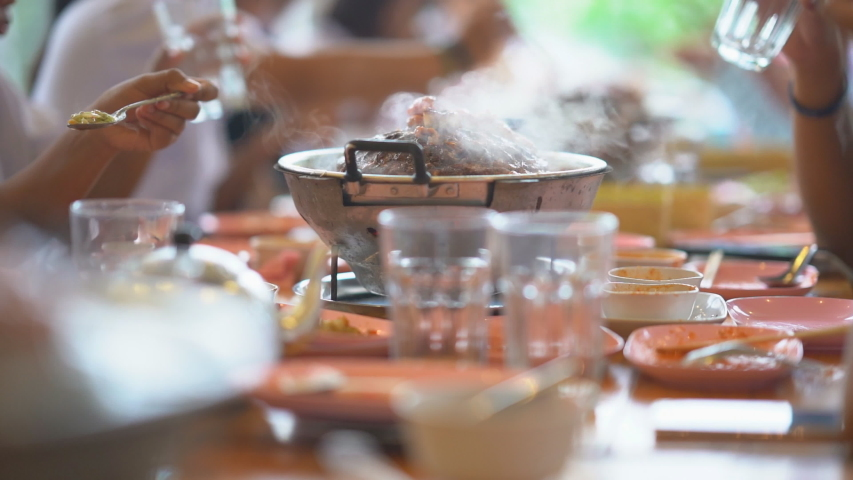 Slow motion pork meat grilled on pan for eating food of people in restaurant, party people person group on meat, hand holding water glass for drinking and spoon for eating food funny and relaxing time | Shutterstock HD Video #1035266357