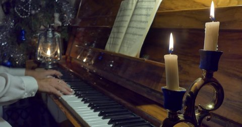 Woman playing piano at Christmas by candlelight and kerosene lantern.