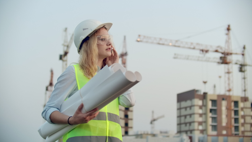 Talking woman in a helmet on the phone on the background of construction with cranes holding drawings in hand. Female engineer on construction site. | Shutterstock HD Video #1035360347