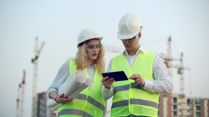 Two industrial engineer wear safety helmet and holding tablet engineering working and talking with drawings inspection. On building outside. Engineering tools | Shutterstock HD Video #1035360407