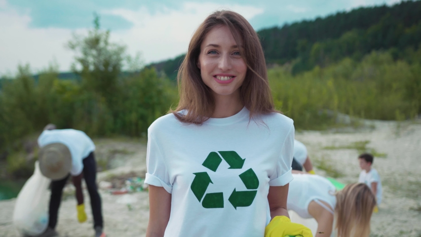 Pretty caucasian girl picking up garbage at sandy beach. Portrait of smiling female eco fighter helping environment cleaning nature from pollution. | Shutterstock HD Video #1035365387