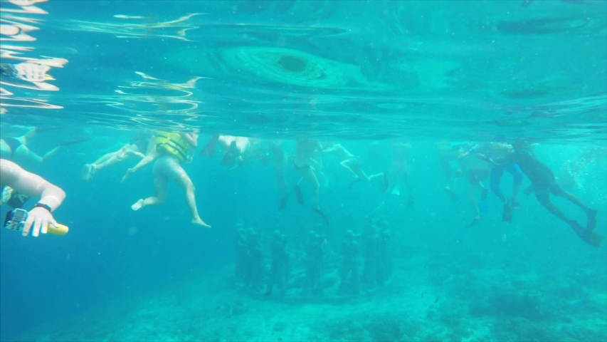 Underwater view of old statues on the sea floor and many tourists snorkling to explore them. Clean balinese water, Indonesia   Shutterstock HD Video #1035417287