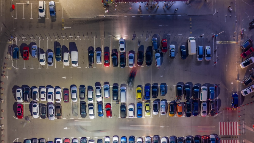 Aerial top view of the supermarket (hypermarket or shopping mall) parking lot with lots of cars at night. Time lapse.    Shutterstock HD Video #1035417557