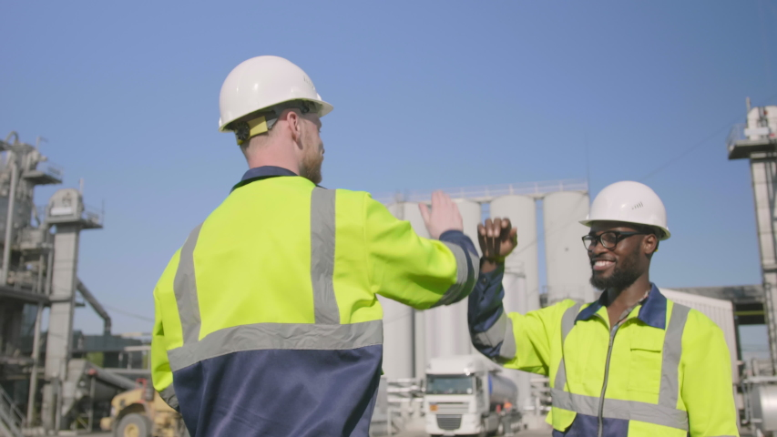 Happy industrial engineers giving high five while working outside at oil refinery #1035420317