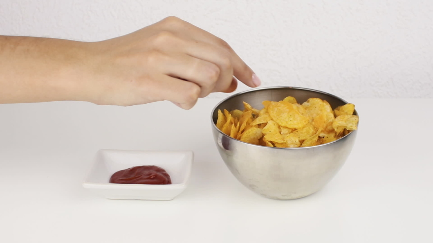 Female beautiful hands with take potato chips from a deep plate. Unhealthy food, fast food   Shutterstock HD Video #1035425387