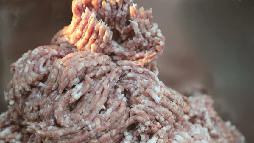 Large industrial meat grinder, grinds the meat into minced meat. Pieces of minced meat come out of the grinder. | Shutterstock HD Video #1035433397