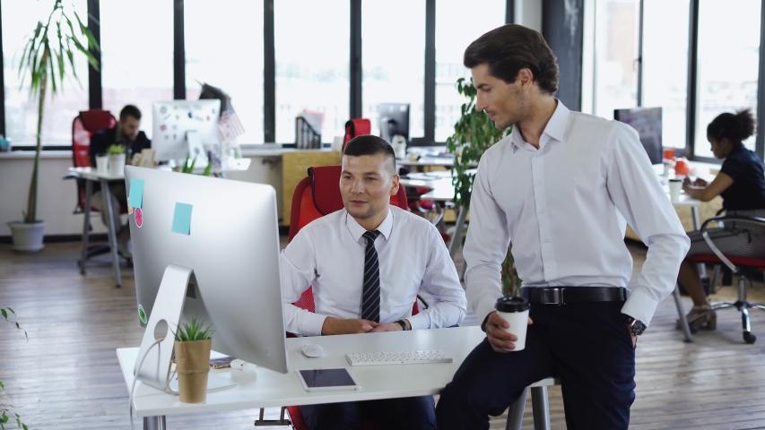 International teamwork in modern office,two men communicate near workplace, asian girl comes to colleagues, financial office workflow. | Shutterstock HD Video #1035438527
