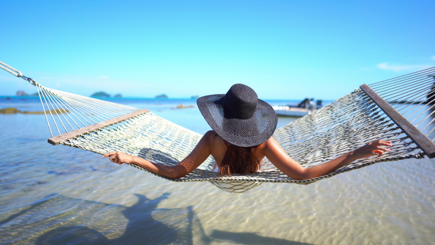Young woman wearing a floppy black straw hat sitting in the sun and swinging in a hammock while looking out at the ocean. | Shutterstock HD Video #1035483317