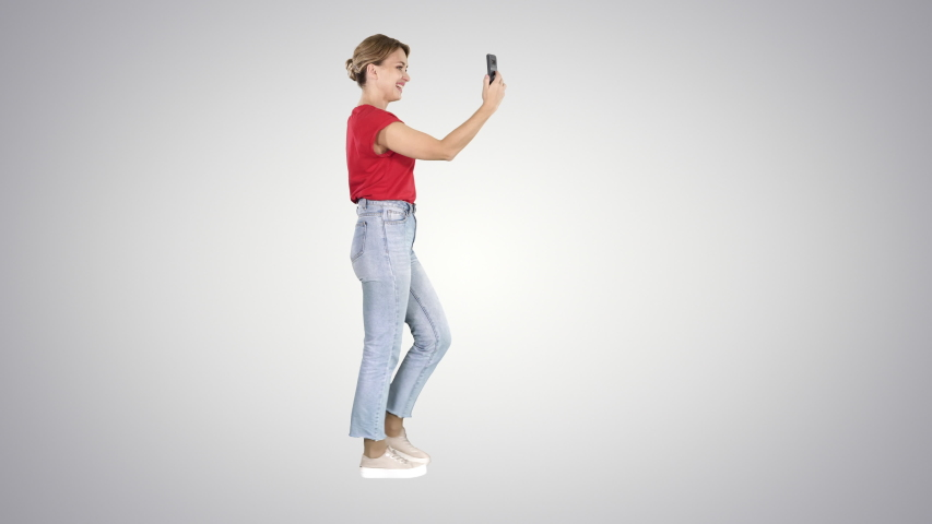 Young cute lady is having video call on her phone Video blog on gradient background. | Shutterstock HD Video #1035489167