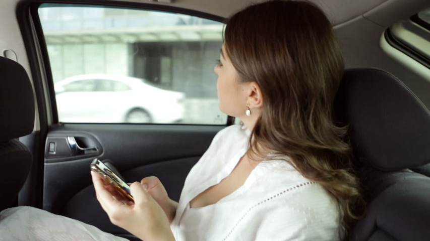 Beautiful woman using cellphone during car backseat ride. Video footage | Shutterstock HD Video #1035510797