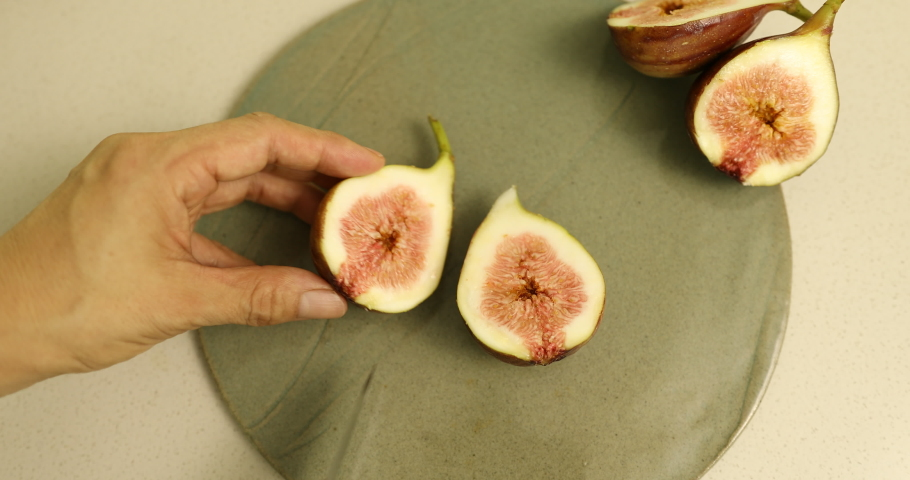Cut ripe fig in half to show texture of inside | Shutterstock HD Video #1035510947