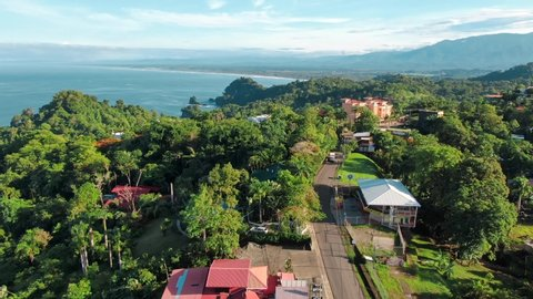 Drone Footage of Main Road in Manuel Antonio Finca, Costa Rica Surrounded by Green Tropical Hills, Houses, and Other Buildings with the Pacific Ocean in the Background on a Sunny and Partly Cloudy Day