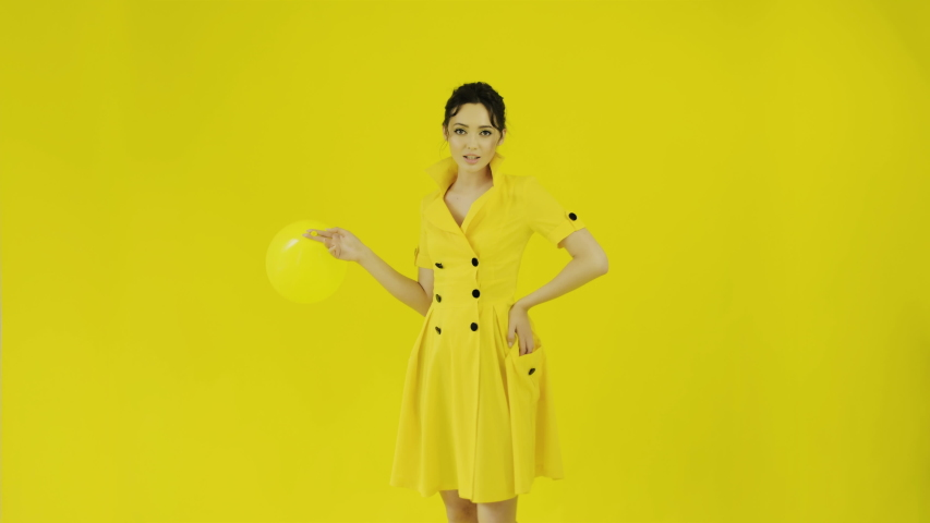 Cheerful beautiful girl in bright stylish yellow dress in studio on yellow background is in hands of yellow balloon. Joyful emotions on face. Concept for advertising. Bright colors. | Shutterstock HD Video #1035655877
