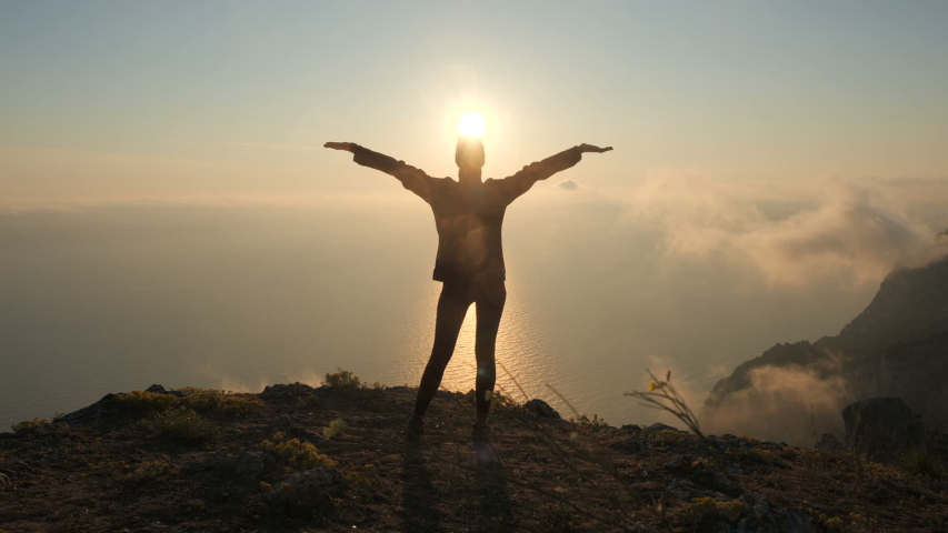 Silhuette Young Woman arms outstretched observing a beautiful dramatic sunset above a sea from a high mountain in Crimea. #1035656777