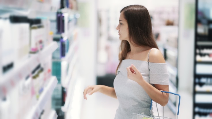 Young woman in cosmetics shop chooses shower gel, reads label, sniffss it, slow motion. Concept of shopping, purchases #1035663497
