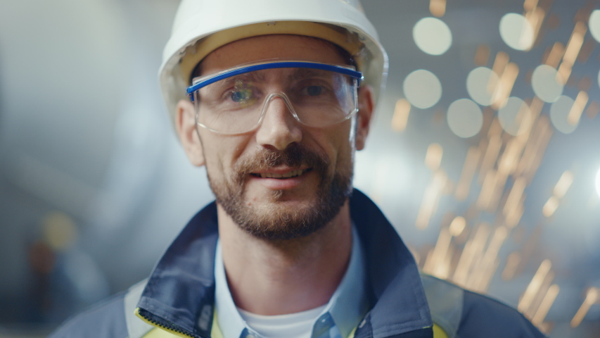 Portrait of Smiling Professional Heavy Industry Engineer / Worker Wearing Safety Uniform, Goggles and Hard Hat. In the Background Unfocused Large Industrial Factory where Welding Sparks Flying | Shutterstock HD Video #1035704117