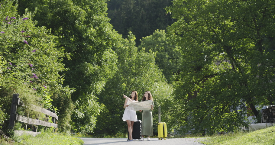 Two girls standing with luggage and map #1035901127