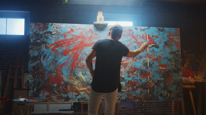Talented Male Artist Energetically and Violently Using Paint Brush he Creates Modern Masterpiece of the Oil Painting. Creative Studio with Large Canvas of Striking Colors. Back View Following Shot | Shutterstock HD Video #1036107737