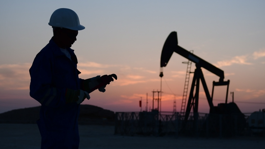 Silhouette of a technical oilfield worker monitoring crude oil pump at sunset.