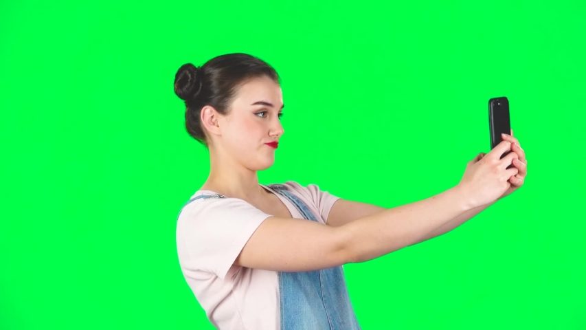 Young woman makes selfie on mobile phone then looking photos on green screen at studio, slow motion. Girl with two hair-buns and red lips, wearing denim overalls and pink t-shirt. | Shutterstock HD Video #1036172297