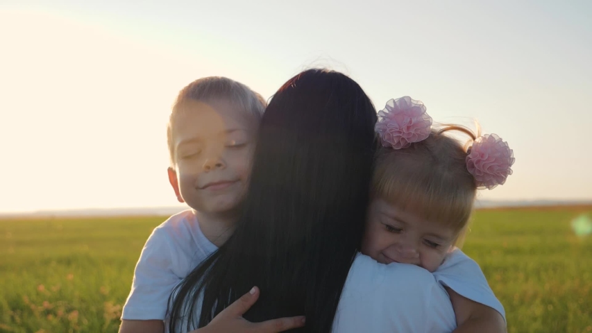 A happy family. A young mother hugs her two young children, laughing in a field in the sun at sunset. Family love concept | Shutterstock HD Video #1036173137