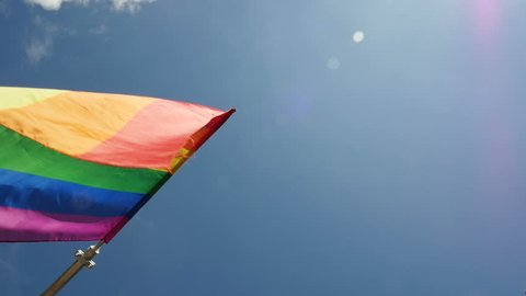 Slow motion of rainbow flag waving against blue sky. Commonly the gay pride flag and sometimes the LGBT pride flag, is a symbol of lesbian, gay, bisexual, and transgender LGBT pride and LGBT movements