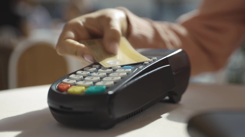 NFC technology. Close-up of young woman using credit card with NFC chip on bank terminal. Customer paying for food order outdoor. | Shutterstock HD Video #1036241147