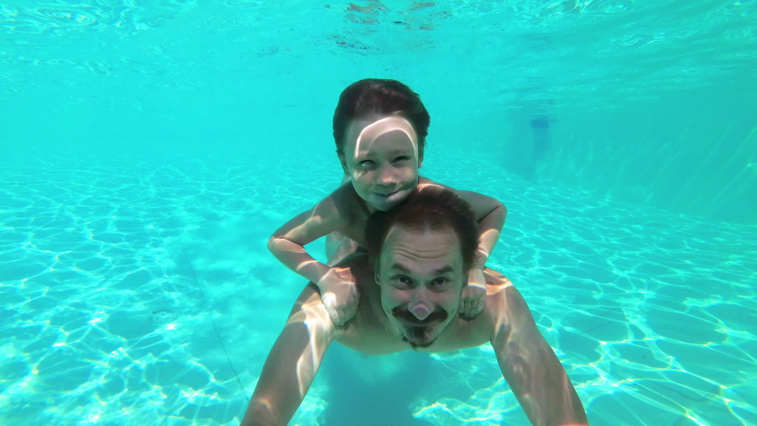 Father and son swimming underwater in swimming pool like a dolphin. Fun weekend in water park spending together. Family concept | Shutterstock HD Video #1036305077