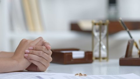 Male giving dollars to ex-wife, engagement rings on table, alimony after divorce