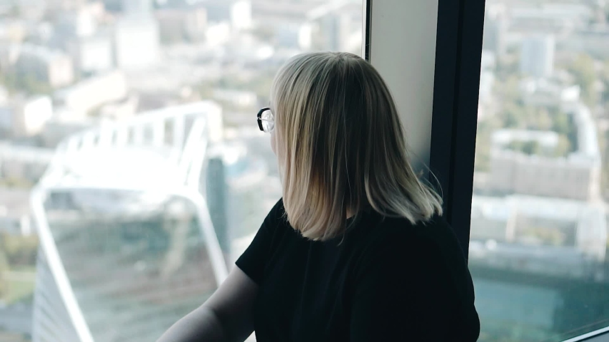 Girl sitting on the floor at the window in a high-rise building. Rear view. Atmospheric shots. | Shutterstock HD Video #1036402997