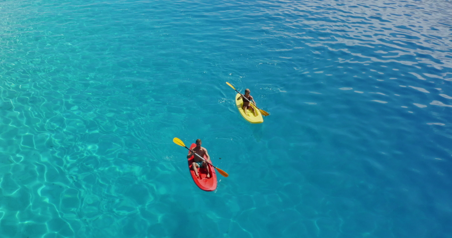 Aerial view of a young couple kayaking together in relaxing blue lagoon water, leisure ocean kayaking