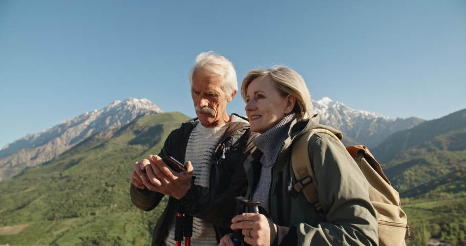 Senior caucasian couple having a nordic walk in mountains, then stopping to take a picture with smartphone. Old people traveling together after retirement - pension, tourism concept 4k #1036468097